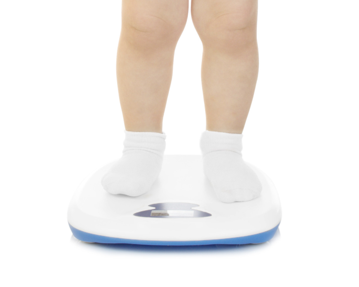 Little funny girl stand on scales